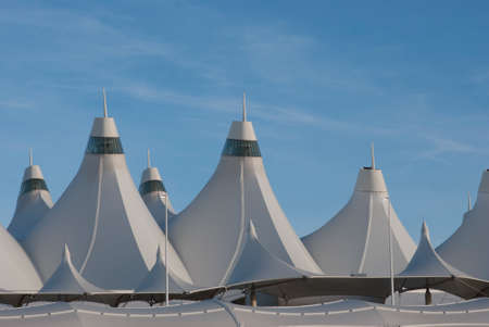 Tent Roofs at Denver Airport during day time.   internationally recognized peaked roof, is reflective of snow-capped mountains and evokes the early history of Colorado Native American teepees
