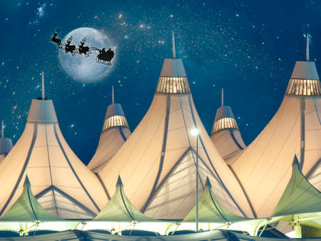 kris kringle: Denver International Airport Illuminated Peaked Roofs against an Evening Sky with a Full Moon and Santa and his Reindeer flying in the sky