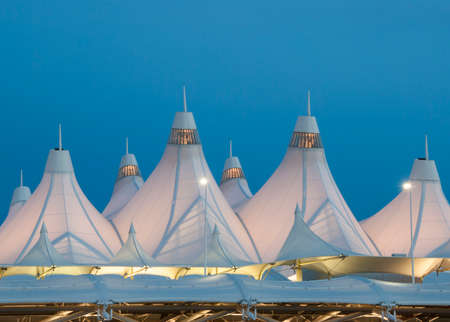 Illuminated Tent Roofs at Denver Airport and Dusk.   internationally recognized peaked roof, is reflective of snow-capped mountains and evokes the early history of Colorado Native American teepees
