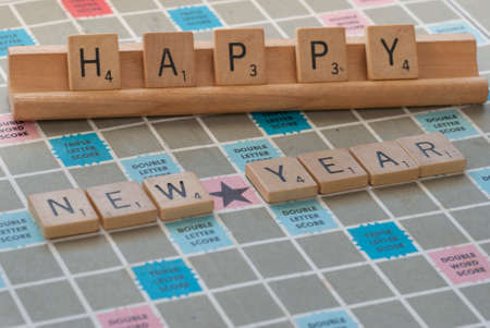 Happy New Year Spelled out in Scrabble Tiles on board with rack Editorial