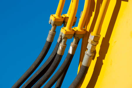 Industrial hose pipes up close of yellow machine against blue sky