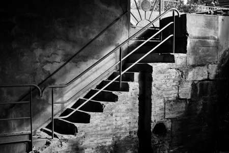 Black and white photograph of a staircase of cut stones, which goes down under a bridge, on a bank. Marked contrasts between shadows and light. Stock Photo
