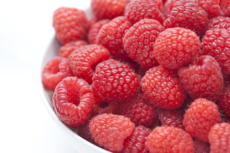 A close up of a bowl of red raspberries