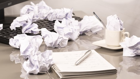 scrunched: Office workplace with book, crumpled paper, pen,  on grey desk Stock Photo