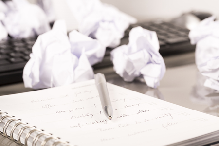 Office workplace with book, crumpled paper, pen,  on grey desk Stock Photo