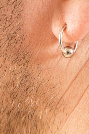 pierced ears: pierced ear of a mature man close-up short beard