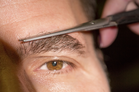 Portrait of man removing eyebrow hairs with scissors
