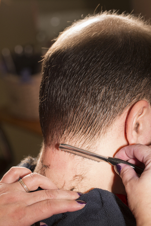 baldness: Hairdresser shaving man with hair trimmer. Baldness