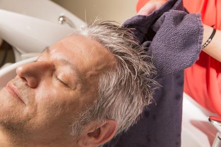 閉じるリラクゼーションで、美容院で hairwash なっている男の顔のアップ。美容師がシャンプーの泡を作る