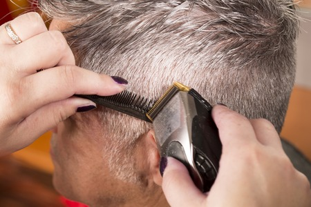 hairdressing scissors: woman cuts hair with scissors, razor in  professional hairdressing salon