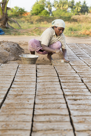 work less: Asia India Tamil Nadu Sengal Soolai village. June 2014. All people of the village work 12 hours a day, 6 days per week, doing hand made bricks for buildings and house. They earn less than 50 dollars per month. Manufacturing of bricks from the beginning to Editorial