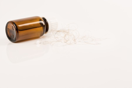 pressure loss: Close-up of  lost brown red hair, treatment homeopathy essential oils plant pills
