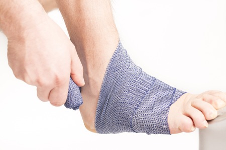 sole on foot: Man doing a bandage on foot ankle white background France