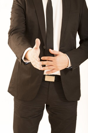 extending: Cropped image of businessman extending hand to shake white background