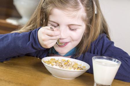 comiendo cereal: Primer plano retrato de la hermosa niña que tiene el desayuno, diferentes sentimientos, comida y bebida concepto, comida sana, de interior