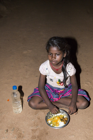underprivileged: Documentary editorial image. Pondicherry, Tamil Nadu, India - April 24 2014. Very poor young girl sitting in the street, eating on the floor during the night. Poverty