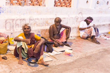 hombre pobre: Documentary editorial image. Pondicherry, Tamil Nadu, India - June 25 2014. Very poor man and woman sitting in the street asking for food. Poverty in the world