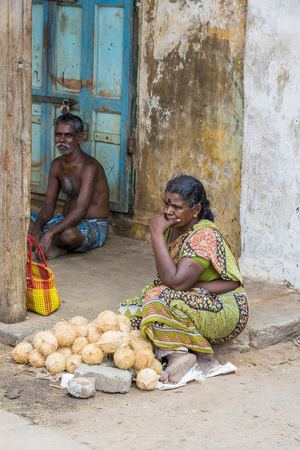 overpopulated: Documentary editorial image. Pondicherry, Tamil Nadu, India - May 28 2014. Very poor man and woman sitting in the street, trying to sell their fruits for money. Poverty in the world