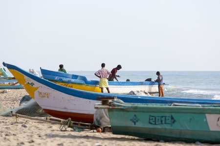 Pondichery, Tamil Nadu, India - February 27, 2014 : Traditional fishermen on beach, on sea, on sand. Long boats, Hard work poor people