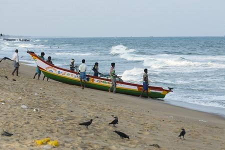 village man: Pondichery, Tamil Nadu, India - February 27, 2014 : Traditional fishermen on beach, on sea, on sand. Long boats, Hard work poor people