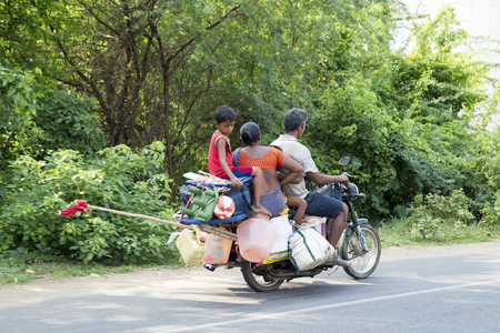 move in: Illustrative image. Pondicherry, Tamil Nadu, India - Marsh 02, 2014. Motorbike, main way to move in the city for families, man, woman