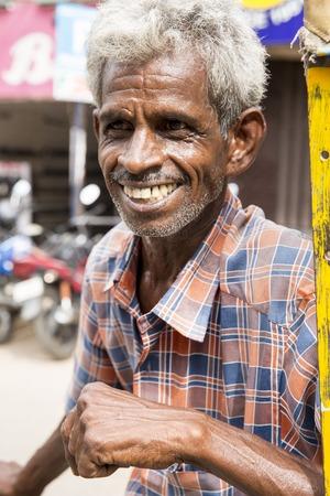 Illustrative image. Pondicherry, Tamil Nadu, India - April 14, 2014. Portrait of senior indian man in traditional costume. Poor men sad smiling sitting