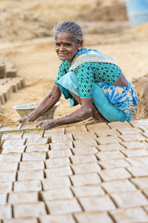 Illustrative image. Pondicherry, Tamil Nadu, India - July 03, 2014. Poor woman worker in small village, very hard work for little money roupies