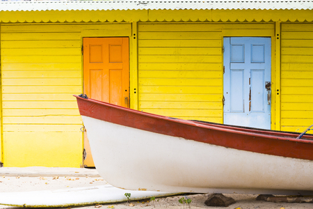 Colored wood house on beach yellow orange with small boat
