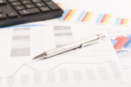 keyword research: Financial printed paper charts, graphs on desk with pen and keyboard