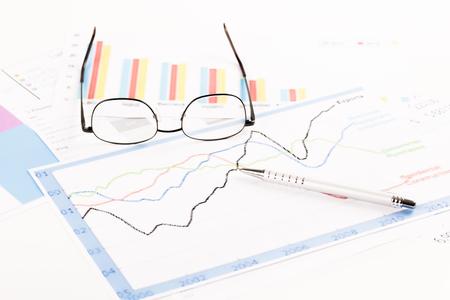 Financiële analyse. Bureau met grafieken pen en bril Stockfoto - 79922877