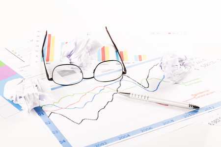 Desk with graphs, keyboard, glasses, pen and shredded papers. Stress at work, burn out