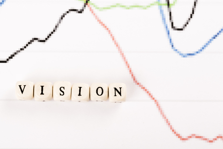 VISION written with wood cubes letters on financial business graph Stock Photo