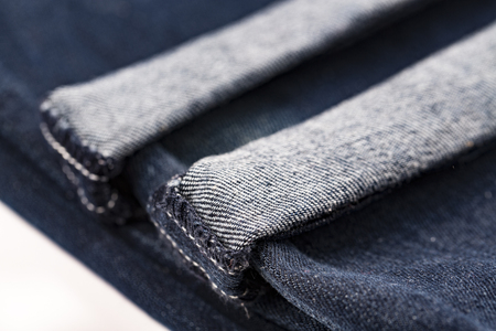 Denim blue jeans folded hemmed close up on with background Stock Photo