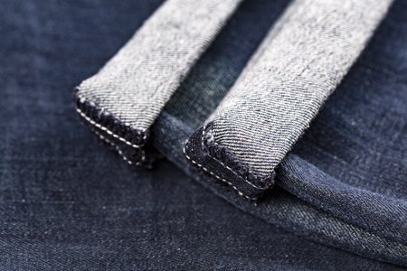 fading: Denim blue jeans folded hemmed close up on with background Stock Photo