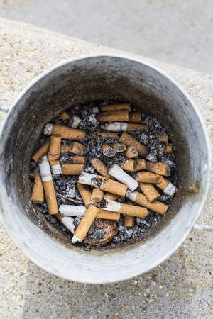 The used cigarettes stub placed on big jar Stock Photo