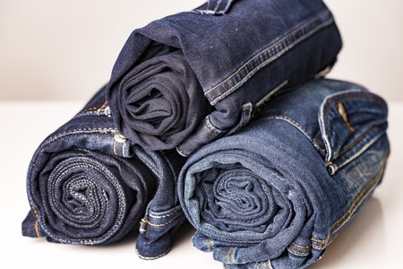 Pile of ree different blue jeans on white table