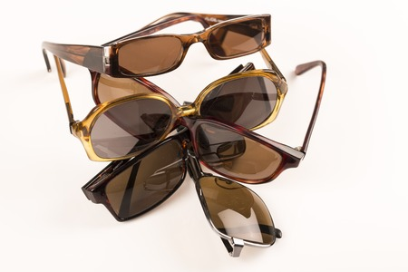 tinted glasses: Cluster, pile of old sun glasses on with table, ready to recycle