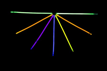 music background: Glow sticks neon light fluorescent on back background. variation of different colored chem lights like the sun or star