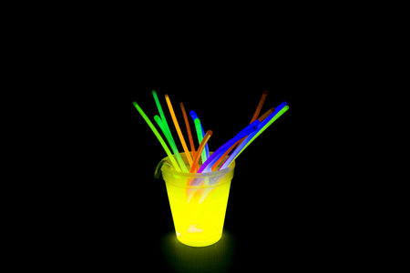 glow stick: Yellow fluorescent glass with glow sticks neon light on back background. variation of different colored chem lights