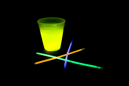 music background: Yellow fluorescent glass with glow sticks neon light on back background. variation of different colored chem lights