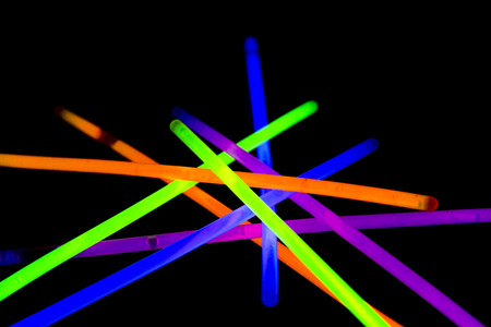 music background: Glow sticks neon light fluorescent on back background. variation of different colored chem lights