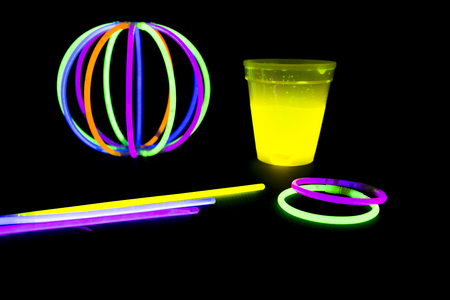 glow stick: Yellow fluorescent glass and ball with glow sticks neon light on back background. variation of different colored chem lights Stock Photo