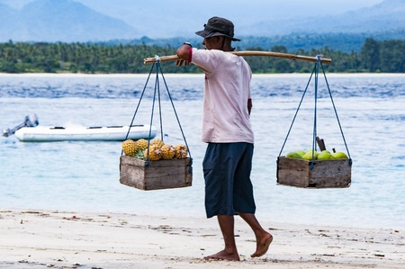Gili Air, Bali, Indonesia - July 21, 2013. Street vendor, traveling salesman on the beach saling pineapple 新闻类图片