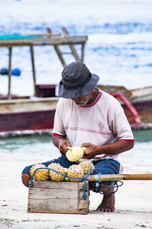 seller: Gili Air, Bali, Indonesia - July 21, 2013. Street vendor, traveling salesman on the beach saling pineapple Editorial