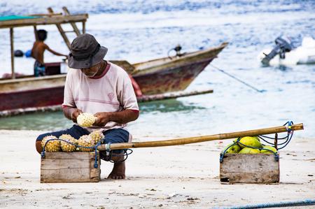 fish vendor: Gili Air, Bali, Indonesia - July 21, 2013. Street vendor, traveling salesman on the beach saling pineapple Editorial