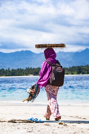 travelling salesman: Gili Air, Bali, Indonesia - July 21, 2013. Street vendor, traveling saleswoman on the beach saling jewels