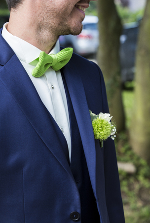 Groom with blue suit and green apple tie close up