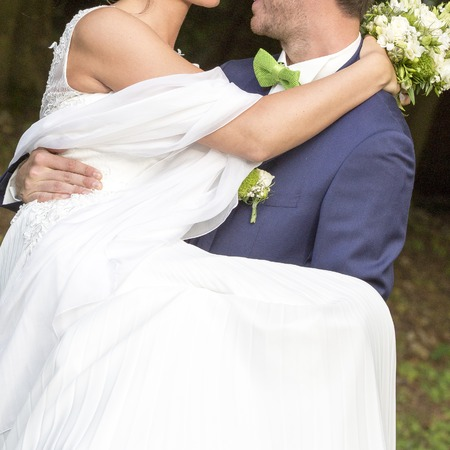 Groom carrying Bride in the garden close up Stock Photo