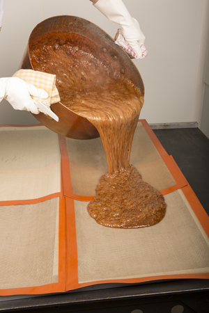 Factory of the production of delicious caramel candies. second step. brown caramel fudge dispensing, pourring on the pad. Close up, with the hands of the employee