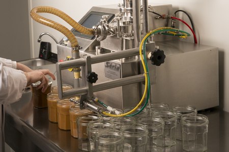 Automated food factory machine get the caramel jam in the jugs. Close up